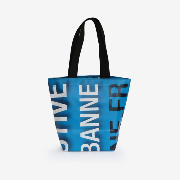 Dos sac cabas bleu et graphique en bâche publicitaire