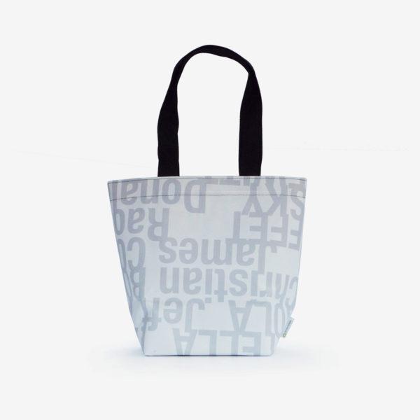 Dos de sac de fille en bâche publicitaire blanche avec lettres grises.
