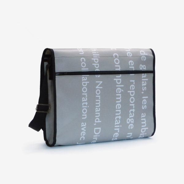 Dos de sacoche en bâche publicitaire grise et textes blancs.